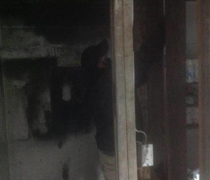 SERVPRO Employee cleaning soot off of affected materials and walls.